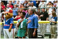 President Bush starts off the first game of the 2004 White House Tee Ball season with the pledge of allegiance June 13, 2004. Standing with the President are members of Girl Scout Troop.