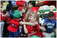 A young ballplayer from the West University Little League Challengers from Houston, Texas, cheers with her team Sunday, July 24, 2005, at a Tee Ball game on the South Lawn of the White House.