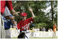 A player from the West University Little League Challengers from Houston, Texas, is welcomed as he crosses homeplate to score a run, Sunday, July 24, 2005, during a Tee Ball game on the South Lawn of the White House.