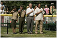 """President George W. Bush is joined by Barry Larkin, White House Tee Ball Commissioner of the Game and Young Marines as they stand for the National Anthem Sunday, June 26, 2005, during """"Tee Ball on the South Lawn."""""""