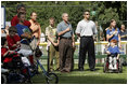 President George W. Bush listens to the National Anthem before a Tee Ball game on the South Lawn of the White House between the District 12 Little League Challengers from Williamsport, PA and the West University Little League Challengers from Houston, Texas on Sunday July 24, 2005.