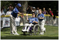 A player from the District 12 Little League Challengers from Williamsport, PA is helped to home plate by her buddy during a Tee Ball game on the South Lawn of the White House on Sunday July 24, 2005.