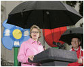 Education Secretary Margaret Spellings and Health and Human Services Secretary Mike Leavitt address soggy visitors to the 2005 White House Easter Egg Roll on the South Lawn Monday, March 28, 2005.^M