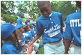 Players congratulate each other in the dugout during the second Tee Ball game on the South Lawn on Sunday, June 3, 2001.