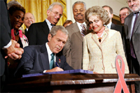 President George W. Bush is joined by Annette Lantos, right, and invited guests Wednesday, July 30, 2008 in the East Room of the White House, as he signs H.R. 5501, the Tom Lantos and Henry J. Hyde Un