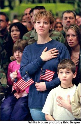 """Family members of Air Force personnel place their hands over their hearts at Elmendorf Air Force Base in Anchorage, Alaska, Feb. 16, 2002. """"I'm honored to be in a place where people understand the need for sacrifice and patriotism,"""" said the President. """"And I've come to Alaska to let you know that I'm proud of our United States military; that when I sent you into action, I knew you would not let this nation down."""