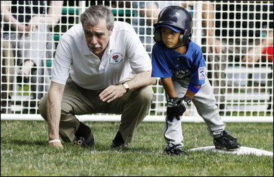 U.S. Secretary of Commerce Carlos Gutierrez coaches a player on third base of the Jose M. Rodriguez Little League Angels of Manatí, Puerto Rico, during the 2008 Tee Ball on the South Lawn Season Opener Monday, June 30, 2008, on the South Lawn of the White House.