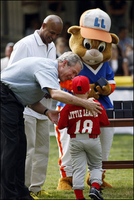 President George W. Bush presents Angel Tavarez, of the Cramer Hill Little League Red Sox from Camden, New Jersey, with a baseball Monday, June 30, 2008, following the opening game of the 2008 Tee Ball on the South Lawn. President Bush is joined on the field by Roberto Clemente, Jr. and Dugout, the Little League mascot.