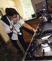 Woman checking for gas leak in cooker