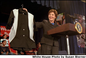 Mrs. Bush displays a sample of the school uniforms that will be made for girls in Afghanistan -- many of whom will attend school for the first time on March 23 when the new school year begins. Mrs. Bush announced a new global partnership of government agencies, private organizations, individuals and corporations to help provide school uniforms and jobs for the women and girls of Afghanistan.