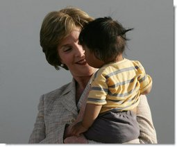 Mrs. Laura Bush smiles as she holds a child during a visit Friday, Nov. 21, 2008, to the San Clemente Health Center in San Clemente, Peru. The center serves an average of 80 patients a day in the town of 25,000 located six miles north of Pisco, the site of the August 2007, 8.0-magnitude earthquake. White House photo by Joyce N. Boghosian