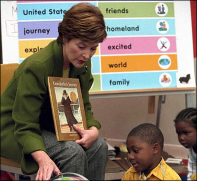 """Laura Bush points uses a globe in her reading of the children's book, """"Grandfather's Journey"""", to students in Mark Williams' kindergarten class at the South 17th Street Elementary School, October 16, 2001."""