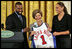 Golden State Warrior Baron Davis, left, and Phoenix Mercury guard Diana Taurasi, right, present Laura Bush with a basketball jersey at the National Book Festival Author's breakfast in the East Room Saturday, Sept. 24, 2005.