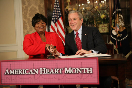 """President George W. Bush shakes the hand of Joyce Cullen, a heart disease survivor, after signing the Presidential Proclamation in Honor of American Heart Month Friday, Feb. 1, 2008, in Kansas City, Mo. In signing the proclamation, the President thanked Mrs. Cullen for her work and said, """".She's very much a part of the Heart Truth Campaign here in Kansas City. And she's helping people understand two things -- one, be able to recognize the symptoms, and secondly, be able to prevent the symptoms from happening in the first place. So I want to thank you for being a strong leader in the campaign for awareness."""" White House photo by Eric Draper"""