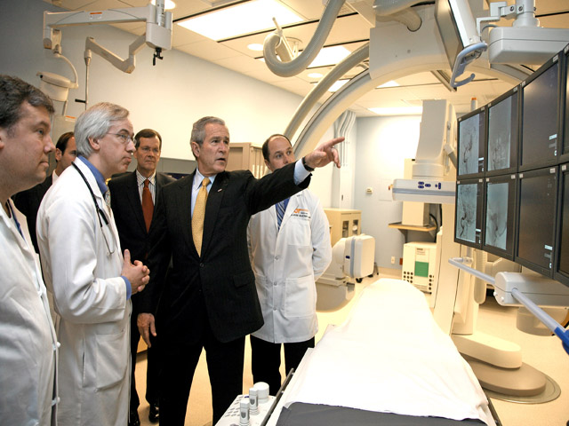 A photograph of President Bush touring a hospital with some doctors, pointing at digital radiology equipment.