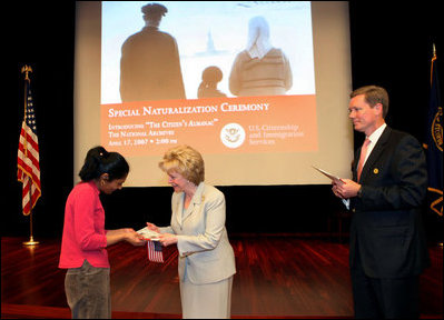 """Mrs. Lynne Cheney hands out a copy of """"The Citizen's Almanac,"""" during a special naturalization ceremony at the National Archives Tuesday, April 17, 2007, in Washington, D.C. White House photo by Lynden Steele"""