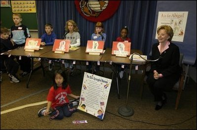 """Lynne Cheney appears as the special guest on WKID, a live televised morning news program for and by Ashurst Elementary School students, on Marine Corps Base, Quantico, Va., Oct. 23, 2003. After singing the Star-Spangled Banner, Mrs. Cheney discussed her two children's books """"America: A Patriotic Primer"""" and """"A is for Abigail: An Almanac of Amazing American Women"""" during the segment titled The Reading Corner. Pictured are the student anchors for the program who are, from left, Micheal Finney, Alexis Till, Breena McCarthy and Amber Warford."""