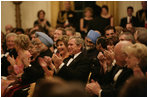 President George W. Bush, Laura Bush and India Prime Minister Dr. Manmohan Singh and Mrs. Gursharan Kaur, applaud the entertainers appearing Monday, July 18, 2005 at the official dinner at the White House. White House photo by Eric Draper