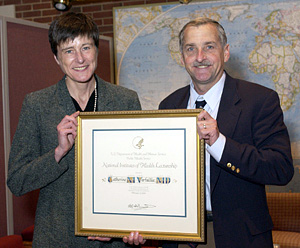 Dr. Catherine Verfaillie accepts a plaque from NIDCD director Dr. James Battey