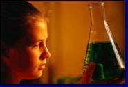 photo of female science student observing liquid in a beaker