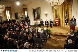 President George W. Bush speaks on stage in the East Room of the White House Tuesday, Jan. 13, 2009, during the Ceremony for the 2009 Recipients of the Presidential Medal of Freedom. With him on stage are the recipients, from left: Former Prime Minister Tony Blair of the United Kingdom, former Prime Minister John Howard of Australia, and President Alvaro Uribe of Colombia. White House photo by Chris Greenberg