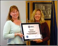 Mayor of Nome, Alaska, Denise Michels (L) receives recognition for her city's CRS achievements from FEMA Regional Administrator Susan Reinertson. FEMA News Photo, Robert Forgit.
