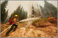 Photo of firefighter spraying water onto Montana wildfire