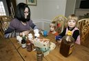 Kristen Kemp, left, has a cup of herbal tea with her three-year-old twin daughters, Annabelle, right, and Estelle at their home in Montclair, N.J., Thursday, Dec. 18, 2008.  Kemp uses home remedies and herbal medicine for her kids' sore throats and colds instead of prescription medications to cut costs.(AP Photo/Mike Derer)