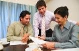 Un hombre sentado, uno de pie, y una mujer sentada en una oficina mirando un documento.
