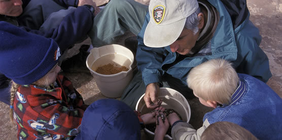 A volunteer assists children during an outdoor education program