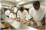 "White House Executive Chef, Cristeta ""Cris"" Comerford, background-left in chef's hat, helps prepare trays of food, Wednesday, Nov. 2, 2005, in the White House kitchen, in preparations for the official dinner for the Prince of Wales and Duchess of Cornwall."