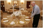 Last minute checks and adjustments are made on the table arrangements in the State Dining Room, Wednesday, Nov. 2, 2005, in preparations for the official dinner for the Prince of Wales and Duchess of Cornwall at the White House.