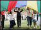 Mrs. Laura Bush participates in playing with a colorful parachute with children and staff outside the Meadowbrook Collaborative Community Center, Tuesday, June 6, 2006 in St. Louis Park. Minn. White House photo by Shealah Craighead