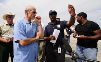 Homeland Security Secretary Michael Chertoff (left) being briefed by Eric Smith (right) FEMA Assistant Administrator for Logistics at the Reliance Center Commodity Staging Site (RSA) in Houston. The RSA is dispatching trucks of ice, bottled water, and Meals Ready to Eat (MRE) to Points of Distribution (POD) in the Houston area in the aftermath of Hurricane Ike. Mike Moore/FEMA