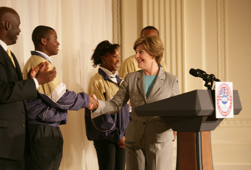 Mrs. Laura Bush is joined on stage by Ballou High School Marching Band Director Darrell Watson, left, as she greets band members Lewis Franklin, Rhia Hardman and Kenneth Horne, right, at the White House Thursday, Oct. 11, 2007, prior to a screening of Ballou: A Documentary Film, about the Washington, D.C. band's inspiring accomplishments for the students and their school. White House photo by Shealah Craighead