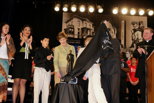 Mrs. Laura Bush flanked by students and Family teachers is presented the Father Flanagan Award during a visit to the Father Flanagan's Girls & Boys Town in Omaha, NE, Monday, April 3, 2006. White House photo by Shealah Craighead
