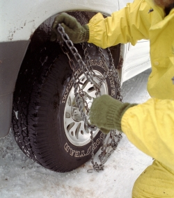 Picture of person putting on snow chains.