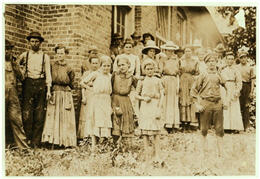 A group of mill workers mostly women and young girls standing in front of a building on the Mill grounds.