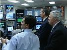Secretary Leavitt and Commissioner von Eschenbach looking at monintors in a FedEx control room. HHS Photo by Holly Babin