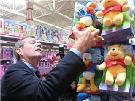 Secretary Leavitt examining a toy at Wal-Mart