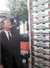 HHS Secretary Leavitt examines stacks of tomato boxes. Photo by Allyson Bell