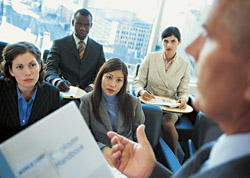 Photo of a group of people listening to a person with a report in hand