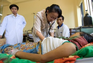 Doctors with a patient and her husband at a Cambodian AITRP hospital site. Photo: David Snyder