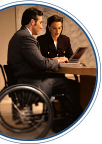 Photo of a man in a wheelchair sitting at a table working on a laptop computer. A woman is sitting next to him.