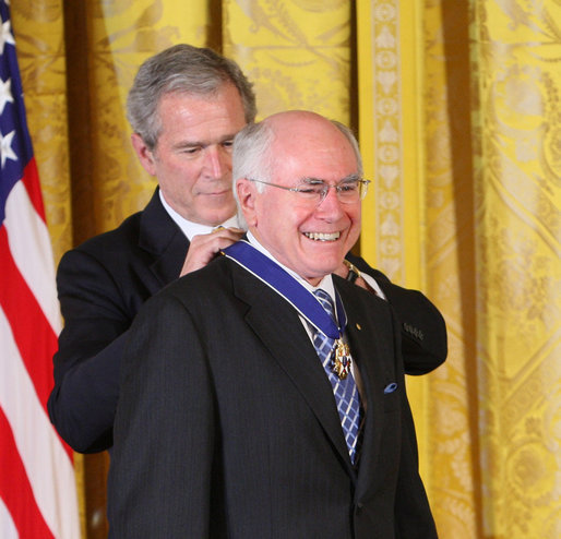 """Former Prime Minister John Howard of Australia, smiles as President George W. Bush presents him with the 2009 Presidential Medal of Freedom Tuesday, Jan. 13, 2009, during ceremonies in the East Room of the White House. Established in 1963, the Medal may be presented to """"any person who has made an especially meritorious contribution to the security or national interests of the United States, or world peace or cultural or other significant public or private endeavors."""" White House photo by Chris Greenberg"""