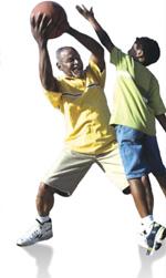 Elderly man playing basketball with a boy