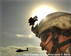 Photograph of a soldier with a helicopter in the sky in the background