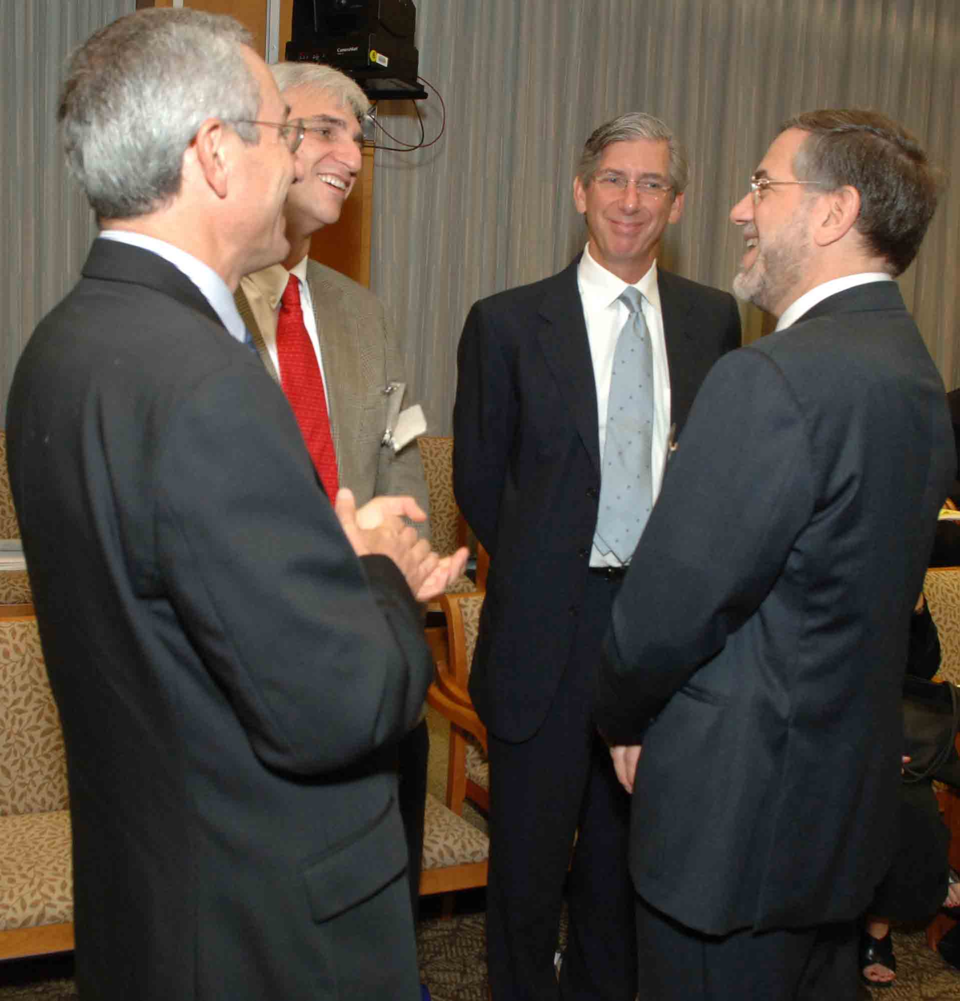 Photo of Doctors Insel and former NIMH Director Steven Hyman, exchange comments with two of the clinical trial presenters-Drs. Gary Sachs and Jeffrey Lieberman
