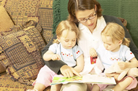 Photo of young twins reading a book with their mother