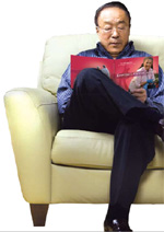 Photo of an elderly Asian man reading the Exercise Guide